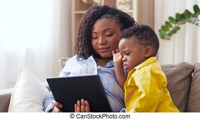 mother using tablet pc with baby son at home - family,...