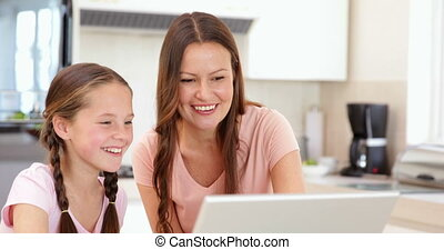 Mother using the laptop with her daughter
