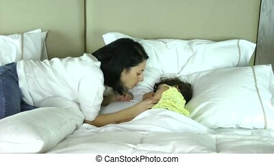 Mother wakes up her daughter in the