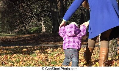 mother walk with little girl walk autumn leaves in park.