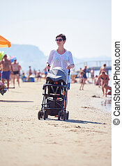 mother walking on beach and push baby carriage
