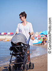 mother walking on beach and push baby carriage - happy young...