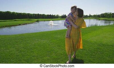 Mother walking on grass embracing toddler daughter
