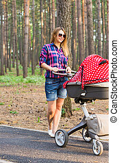 Mother walking with a stroller in the park.