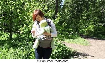 Mother walking with baby in park and rips dandelion