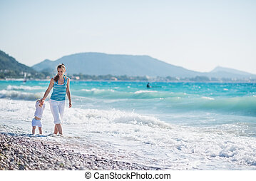Mother walking with baby on seashore