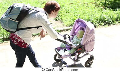 Mother walking with baby with in the stroller in park