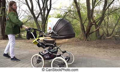 Mother walking with carriage in the park