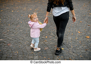 Mother walking with daughter holding her hands in the park