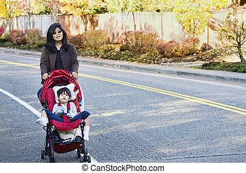 Mother walking with her disabled son in stroller outdoors