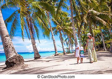Mother walking with her two kids in the palm grove