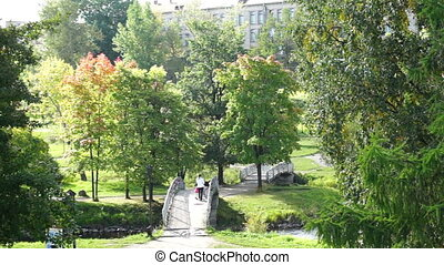 Mother walking with kid in a park near river - PETROZAVODSK,...