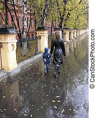 mother walking with son. autumn . rain