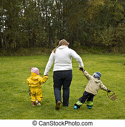 Mother walking with two children. The girl walks nicely by her side, the boy misbehaves.