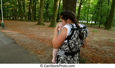 Mother walks in the park with her baby - Beautiful brunette...