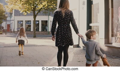 Mother walks together with boy and girl. Holding hands. Woman spends time with little children. Family vacation. 4K.