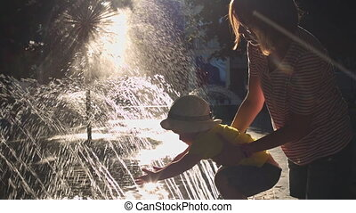 Mother walks with her child in the Park near the fountain