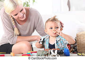 Mother watching son playing with toys