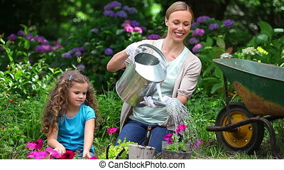 Mother watering flowers while her daughter is watching