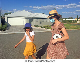 Mother wearing a face mask walking together with her daughter in suburban neighborhood street