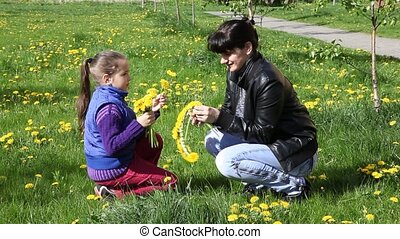 mother weaves a wreath of dandelion - mother in a black...