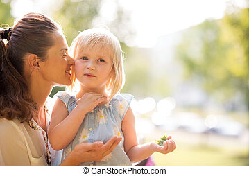 Mother whispering to her daughter in the sunshine in a city ...
