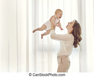 Mother with a baby in her arms plays against the window.
