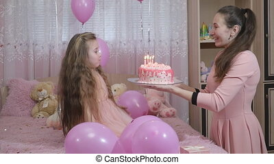mother with a cake comes to her daughter