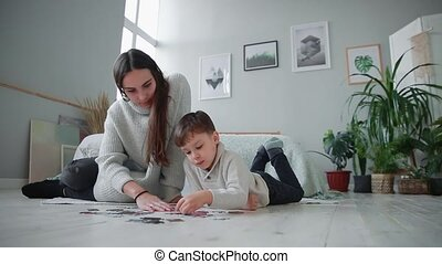 Mother with a child in the white interior of his home to collect the jigsaw puzzle together with his young son. Happy family, educational games.