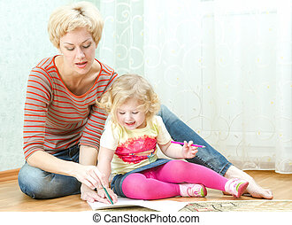 Mother with a little daughter drawing