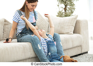 Mother with a little daughter playing on the couch at home.