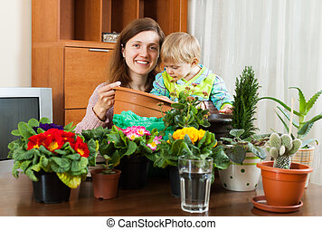 Young mother with a toddler transplanting potted flowers at table in home