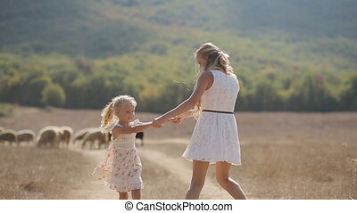 Mother with adorable little daughter holding hands of each other and whirling in slow motion
