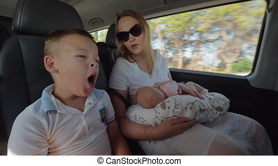 Mother with baby and elder son traveling by car. Boy tired and yawning