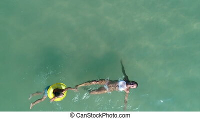 Mother with baby are swimming in a pure blue sea. Drone...