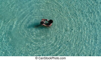 Mother with baby are swimming in a pure blue sea.