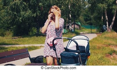 Mother with baby carriage and speaking on phone in summer park. Sunny. Walking