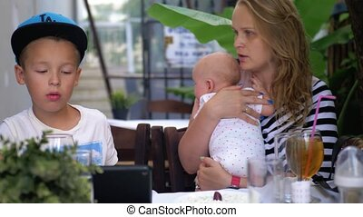 Mother with baby daughter and elder son in street cafe