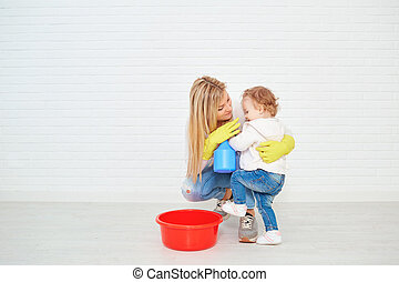 Mother with baby doing cleaning in room.