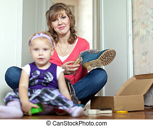 mother with baby girl cleans shoes