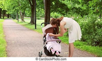 mother with baby girl in stroller at summer park - family,...