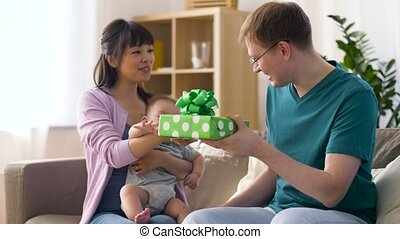mother with baby giving birthday present to father - family,...