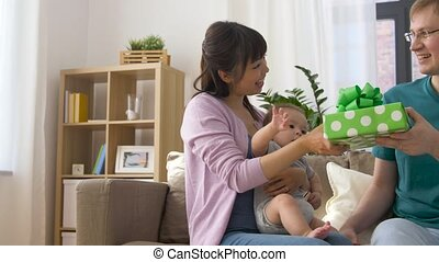 mother with baby giving birthday present to father