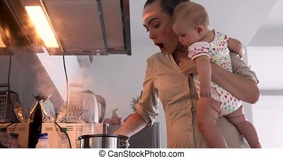 Mother with baby her arms notices burnt porridge - The...