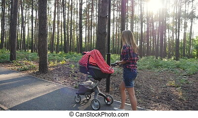 Mother with baby in buggy walking in park