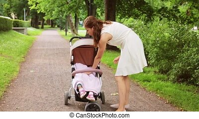 mother with baby in stroller walking at park
