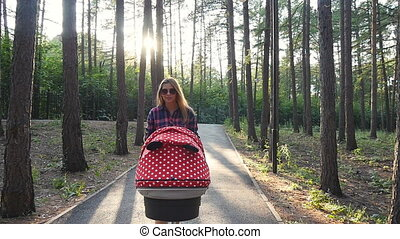Mother with baby in stroller walking in park