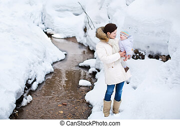 Mother with baby in winter park