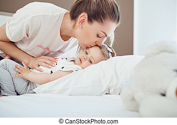 Mother with baby lying on the bed in a room.