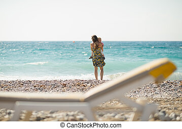 Mother with baby on beach looking into distance. Rear view